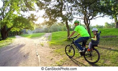 Father With Little Son Riding Bicycle In Green Park - SLOW...