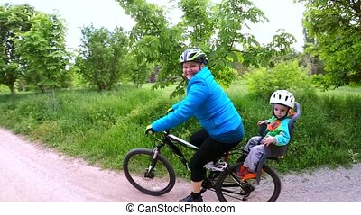 Happy Woman With Two Children Cycling In Green Park - Camera...