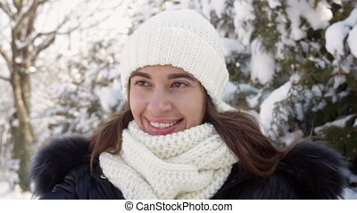 beautiful woman in a knitted hat is walking in the winter...