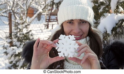 Woman in hat holding snowflake