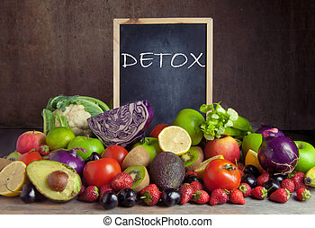 Detox - Fruits and vegetables around a chalkbaord with detox...