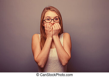 European-looking girl of twenty years surprise, hands face...