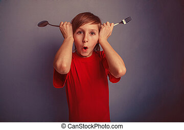 Teenager in red shirt boy twelve years holding spoon and...