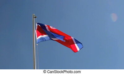 Hoisting a North Korea flag in front of blue sky