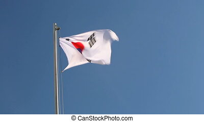 Hoisting a South Korea flag in front of blue sky
