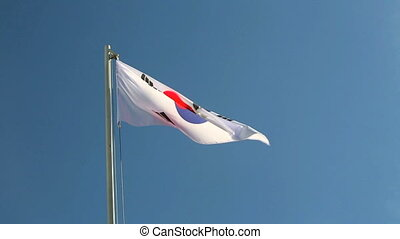 South Korea flag in slow motion in front of blue sky