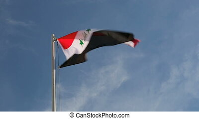 Hoist flag of Iraq in front of a blue sky