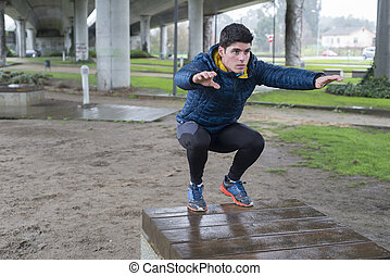 Man squatting in a park on a rainy day
