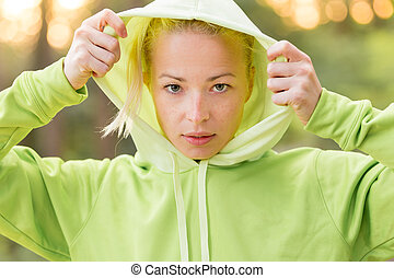Confident sporty woman wearing fashionable green hoodie. -...