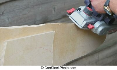 Man planing a plank of wood in his carpentry workshop with a plane to smooth the edge.  Man planed board with Electrical planer