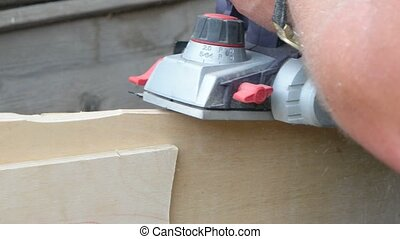 Man planed board with Electrical planer Carpenter working...