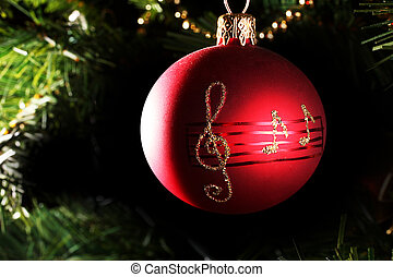 A red christmas bauble with musical notes - A close up of a...