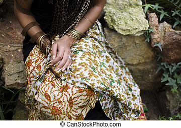 beautiful shot of womans hands in many bracelets sitting on...