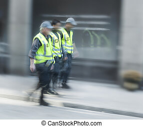 Three security guards in a row walking down the steet
