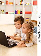 Kids playing computer game on laptop
