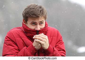 Man shivering in cold winter and rubbing hands while is...