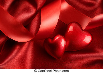 Two red hearts with ribbon on satin background