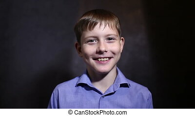 Teen boy says talk talking interview in blue shirt smiling...