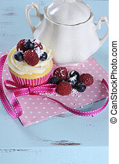 Delicious cupcake with berries and vintage sugar bowl on retro aqua blue shabby chic table, with copy space for your text here.