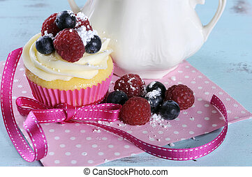 Delicious cupcake with berries and vintage sugar bowl on retro aqua blue shabby chic table