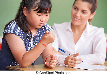 Asian kid at school learning math with teacher
