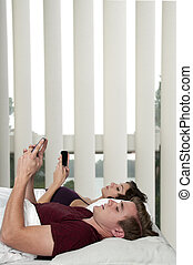 Couple texting in bed - Young married couple texting in bed