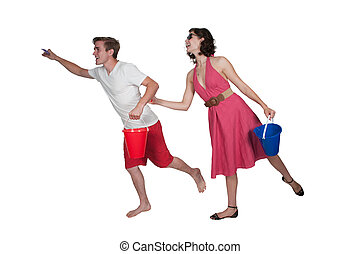 Couple running with a sand pail - Young couple running on...