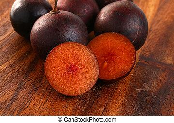 Flacourtia fruit Ramontchi on wood.