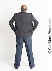 Rear view full length mature Indian businessman looking up -...