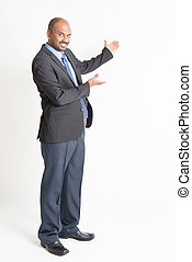 Full length mature Indian businessman showing blank space -...
