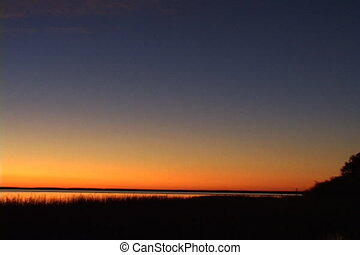 Pan To Lighthouse - Pan across a sunset landscape to a...
