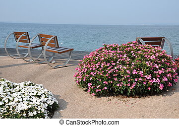Empty benches anf flowers on lakeshore of Garda lake,...
