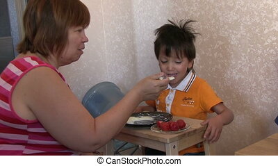 Grandmother With Her Grandson - Grandmother feeding her...