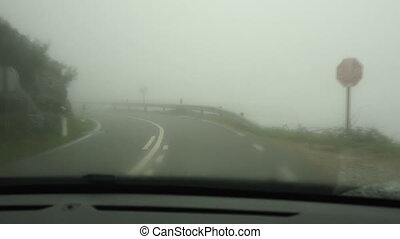 Car driving the Fog Road - Frontal view of a road from...