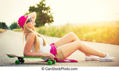 Attractive smiling hipster teenage girl with skateboard,...