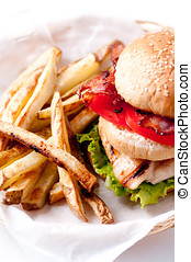 clubhouse sandwich on a burger bun with crispy fries and...