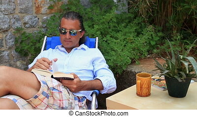 Man reading a book in the garden and drinking coffee