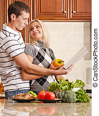 Young Couple Cooking - Young woman looks back affectionately...