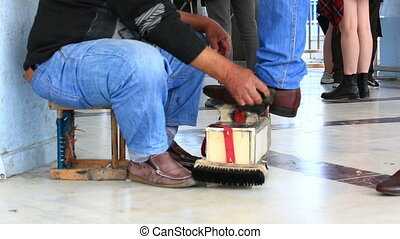 Shoe polisher working in public crowded place - ISTANBUL,...
