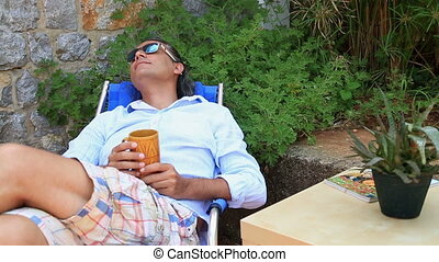Man resting in the garden and drinking coffee