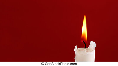 Candle - The top of a white burning candle with a flame on...