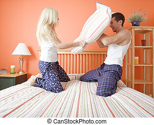 Young Couple Kneeling on Bed Having a Pillow Fight - Young...
