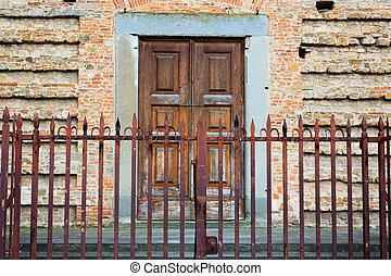 Closed door - A close up of a closed door behind a fence