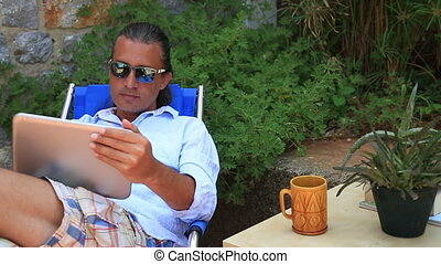 Man using digital tablet in the garden