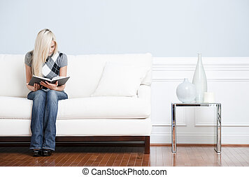 Young Woman Sitting on Sofa Reading - Young woman in...