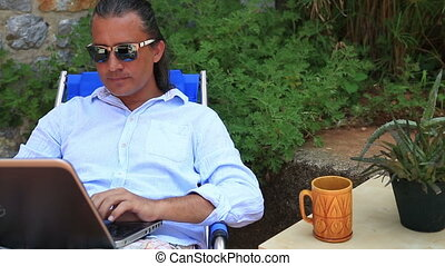 Man using laptop at the garden and smiling