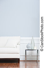 White Sofa and Glass End Table Against Blue Wall - White...