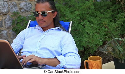 Man using laptop at the garden and drinking coffee
