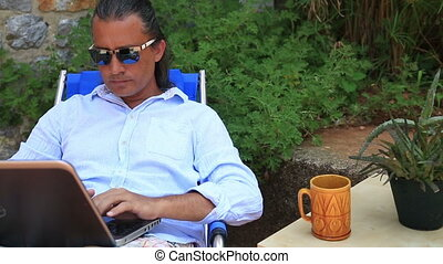Man working with laptop in the garden