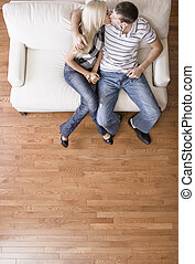 Young Couple Sitting on Love Seat Kissing